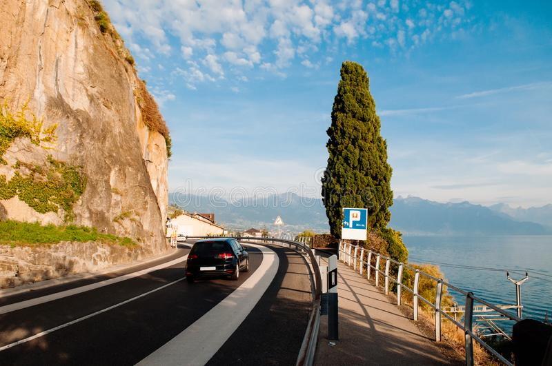 Lake side road by rock cliff in Chexbres village, Vevey, Switzerland. Switzerland - Car on lake Geneva view road with rock cliff in Chexbres village near Vevey royalty free stock image