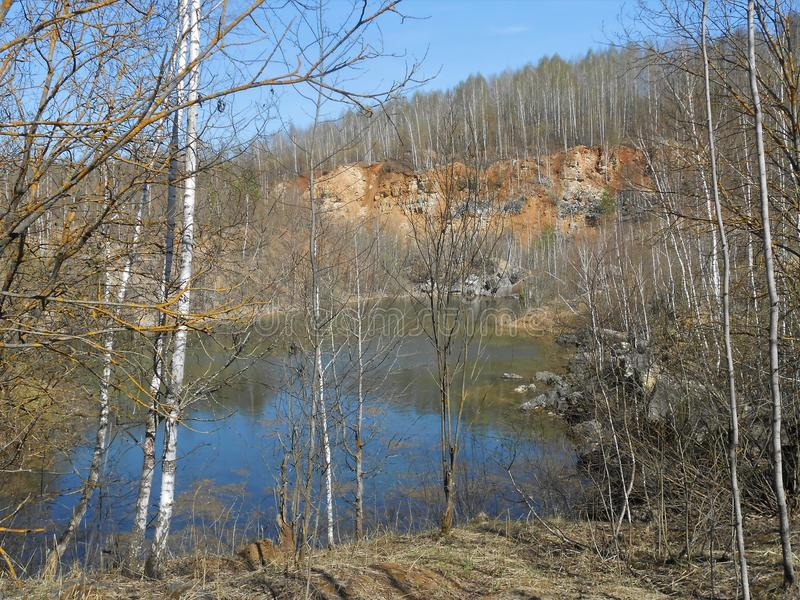 Lake and stones. Landscape with lake with high stoned shores in clear day in springtime. Forest wall on the horizon on the top of shore, young birches on the stock image