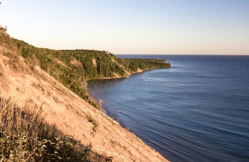 Lake Superior Cliff Seascape On Michigan Coast. Massive sand dune towers above the blue water of Lake Superior in the Pictured Rocks National Lakeshore in Grand stock photos