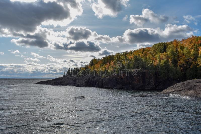 Sun shining on trees changing colors along Lake Superior coastline. Lake Superior coastline Presque Isle, Marquette, Michigan. Sun shining through the clouds on royalty free stock photo