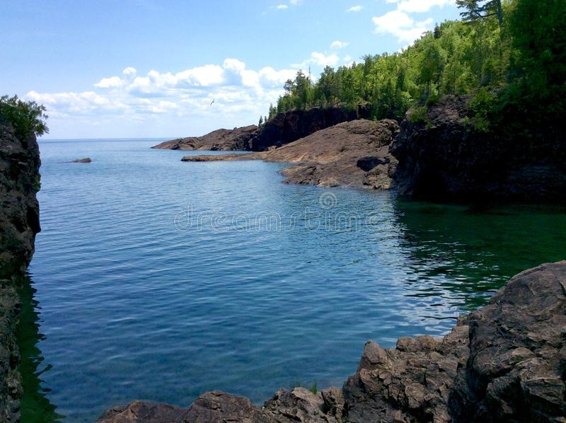 Lake Superior Cove. Amidst the black rocks in Marquette Michigan along the shore of Lake Superior in the peak of summer stock photo