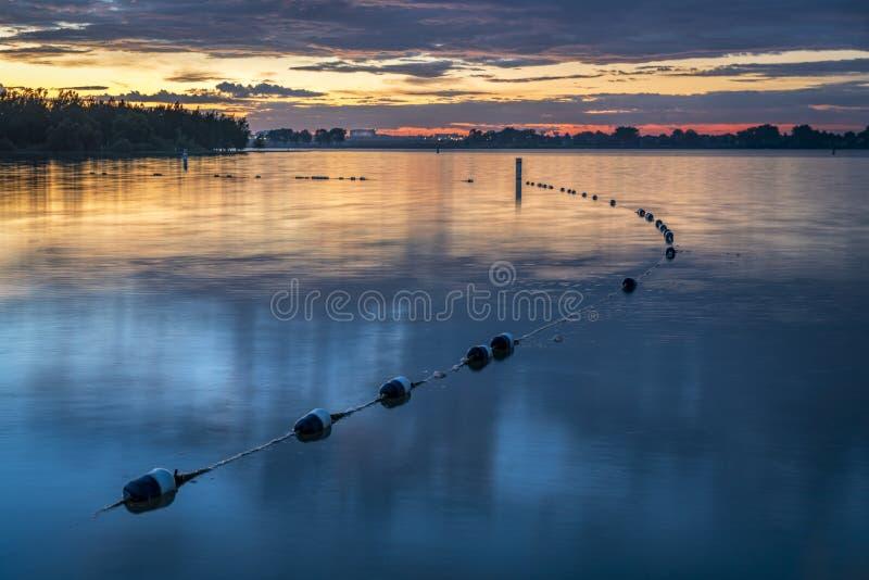 Lake swimming beach at dawn. Dawn over a swimming beach at Boyd Lake State Park, Colorado royalty free stock photos