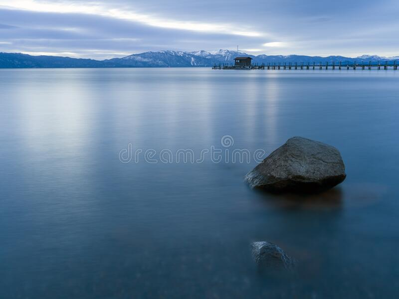 Lake Tahoe in the winter long exposure photograph. Lake Tahoe in the winter long exposure photograph with rocks in the smooth water a pier and snowcapped royalty free stock image