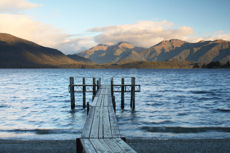 Lake Te Anau. A pier stretches into Lake Te Anau. Lake Te Anau is the gateway for World Famous Hikes, such as The Milford Track and The Kepler Track stock photo