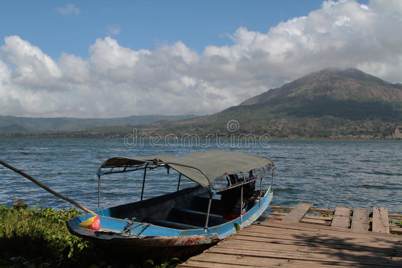 Lake and volcano Batur. Small boat on lake Batur, with volcano landscape royalty free stock photos