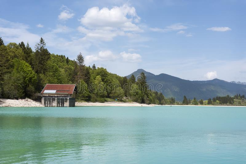 Lake Walchensee with boathouse and mountain range - Typical alpine lake in the bavarian Alps with incredible clear and turquoise stock photo