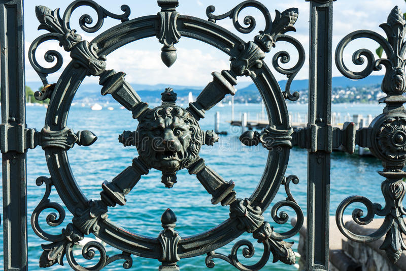 Download lake water seen through iron metal fence with historic decoration in form of a lion