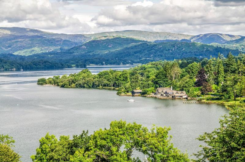Lake Windermere with boathouses. Lake Windermere in the English Lake district showing a tranquil bay with jetty cottages and a boathouse, trees and distant hills royalty free stock image