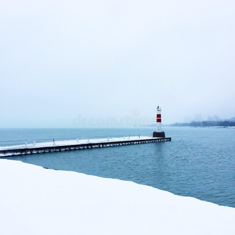 Lake during the winter. Lake winter harbor lighthouse snow stock photos