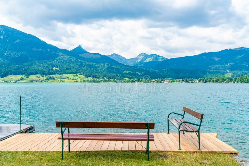 Lake Wolfgangsee, Austria. Benches on wooden deck by Lake Wolfgangsee in the Salzkammergut resort region, Austria royalty free stock photography