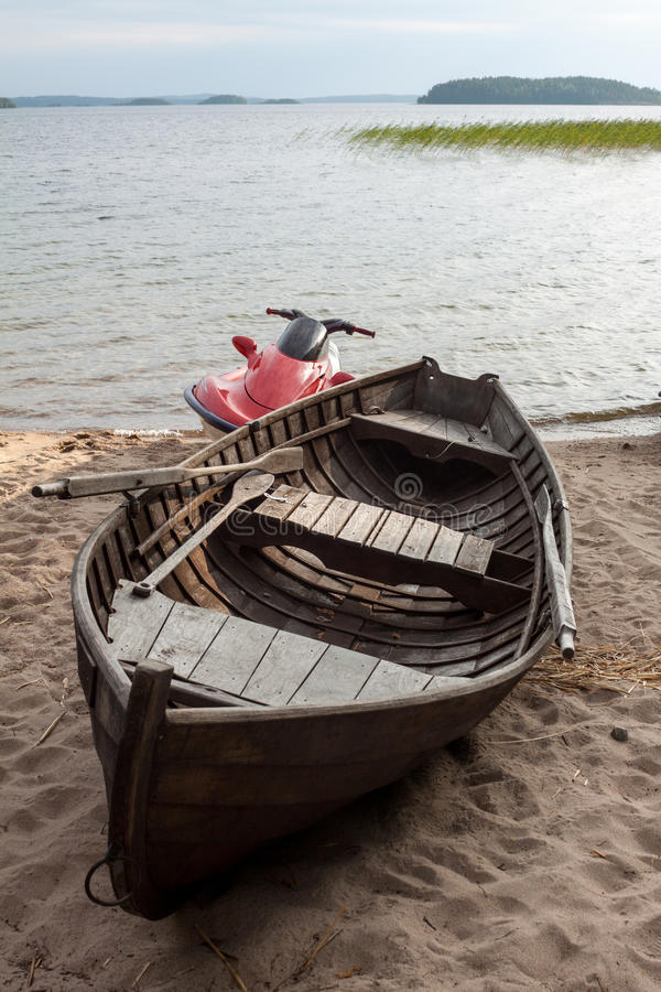 Wooden boat and hydrocycle. Lake with a wooden boat and hydrocycle in Finland royalty free stock photo