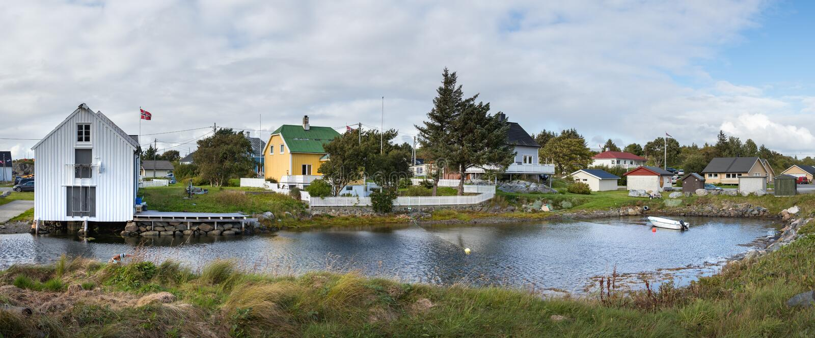 A lake and wooden local houses at the village of Dyrnes at Smola island, Norway. Dyrnes, Smola, Norway - August 30th, 2018: A lake and wooden local houses at the royalty free stock images