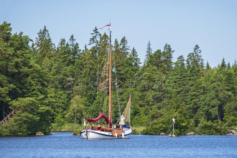 Lake in a woodland with a beautiful old sailboat stock photography