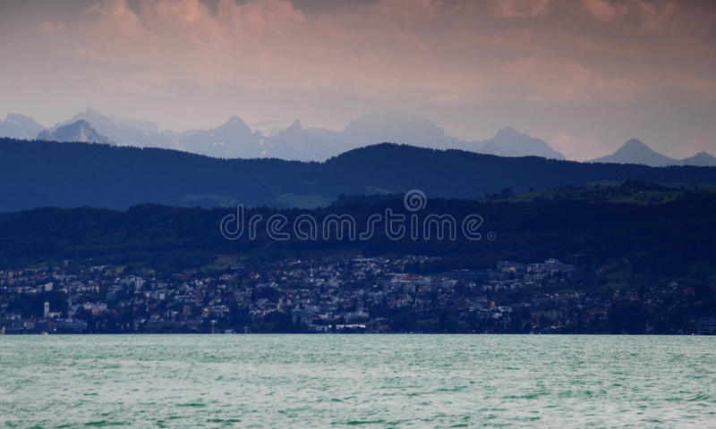 Lake Zurich with hills, mountains and Glarner Alps, Switzerland. On the shore of Lake Zurich the suburb Horgen with green hills, mountains and jagged Glarner royalty free stock photos