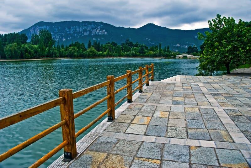Lakeshore près d'une montagne le jour nuageux images libres de droits