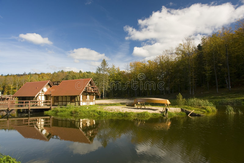 Lakeside chalets. A view of buildings on the side of a small lake or pond in a wooded setting with a canoe upside down on a small boat rack at the water's edge stock photo