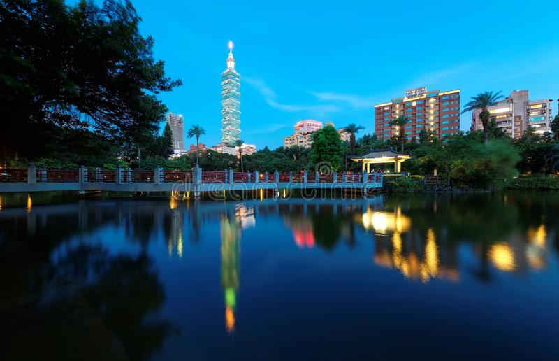 Lakeside scenery of Taipei 101 Tower among skyscrapers in Xinyi District Downtown at dusk with view of reflections on the pond stock photography