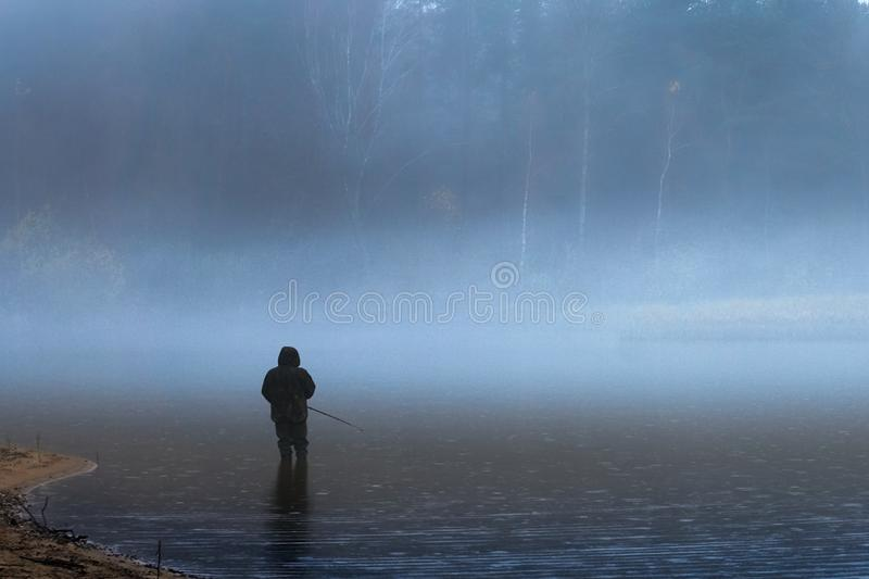 Lakeside shore and islands hidden behind thick fog. Stones on the coast; sand and pebble beach; silhouette of a lone fisherman with a fishing rod. Early royalty free stock photo