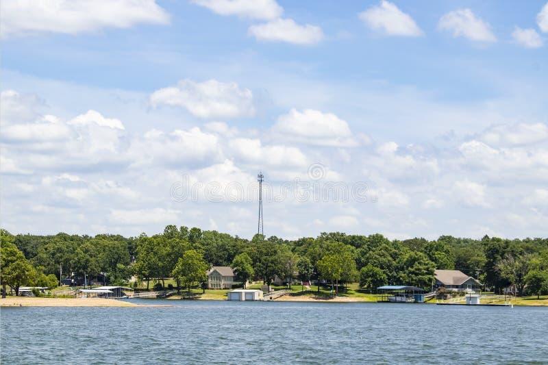 Lakesiden returnerar, och fartygskeppsdockor med träd och en sändare står högt i bakgrunden under en blå himmel med fluffiga moln fotografering för bildbyråer