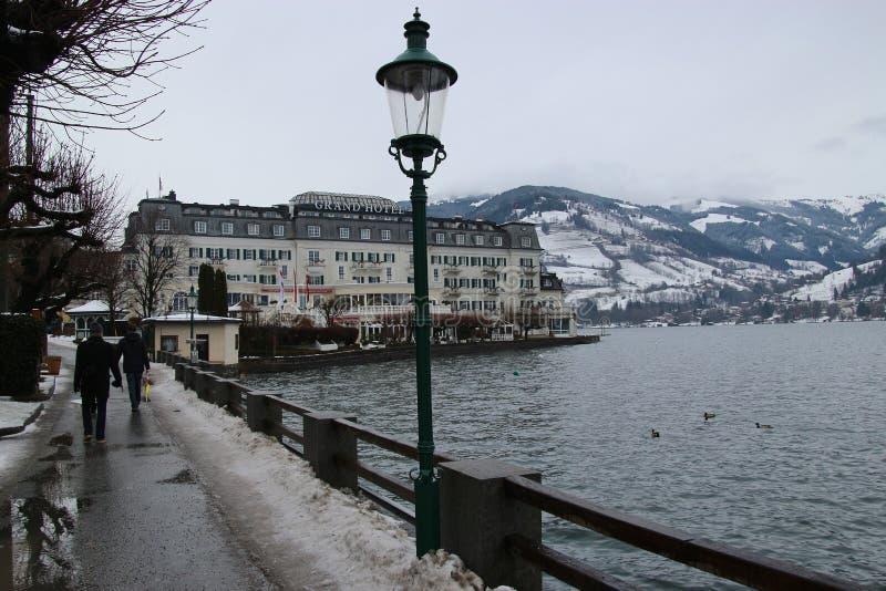 Lakesidepromenad och det storslagna hotellet för adelsman på sjön Zeller ser, Österrike arkivbild