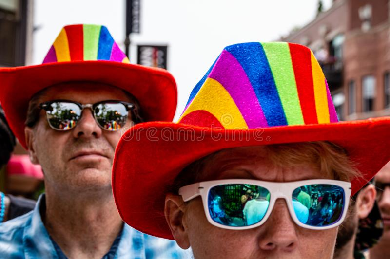 A woman and man are wearing sunglasses and matching rainbow hats to show LGBTQ support at Gay Pride. Lakeview, Chicago-June 30, 2019: A woman and a man are royalty free stock images