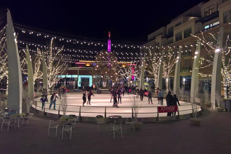 Outdoor ice skating rink at night. LAKEWOOD, CO - JANUARY 07, 2018: People enjoy the festive holiday lights and outdoor ice skating rink at the Belmar shopping royalty free stock photography
