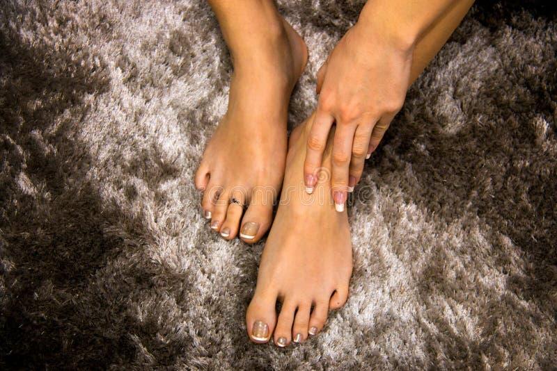 Lakken de goed gegeven sexy vrouwenvoeten vanaf bovenkant met Franse manicure op tenen, hand wat betreft huid, boven menings abst royalty-vrije stock foto