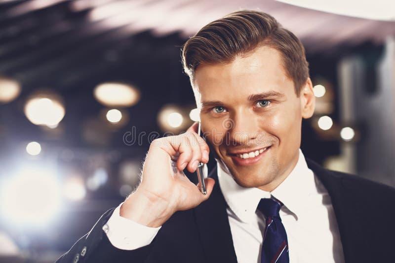 Lakoniczny portret przystojnego młodego mężczyzny rozmawiającego przez telefon i uśmiechającego się obraz royalty free