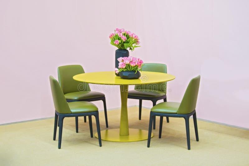 Lakonischer Innenraum des Esszimmers Gelbe Rundtisch- und Grünlederstühle, Vase mit Blumen auf dem Tisch Isolat auf Rosa lizenzfreies stockfoto