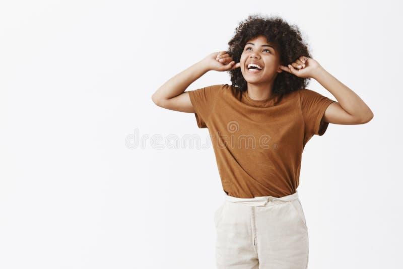 Lalala não pode ouvi-lo Retrato da menina afro-americano nova indiferente e feliz despreocupada na coberta marrom do t-shirt imagens de stock royalty free