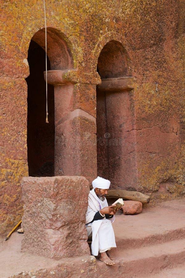 Pilgrim reads bible at the entrance to the unique monolithic rock-hewn church in Lalibela, Ethiopia. UNESCO World Heritage site. Lalibela, Ethiopia - January 27 stock photos