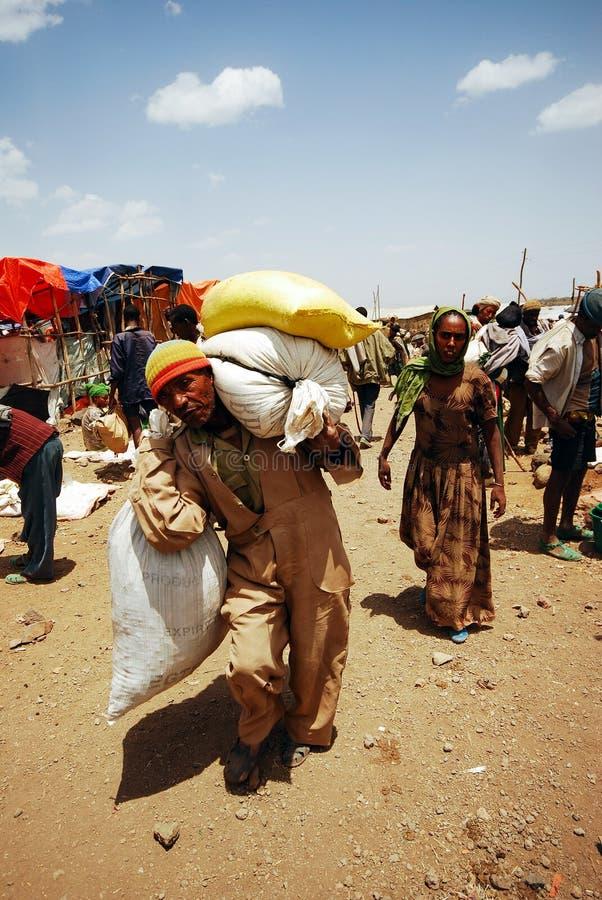 Lalibela Etiopien, 13th Juni 2009: Gamal man som bär den tunga påfyllningen fotografering för bildbyråer