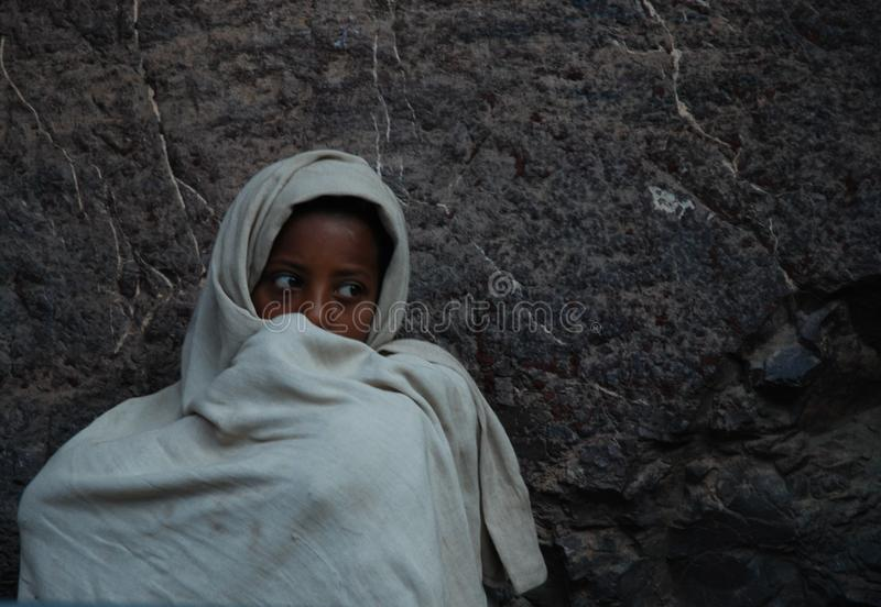Lalibela, Wollo, Ethiopia, circa February 2007: Boy staring while attending religious service. Outside of rock hewn church stock images