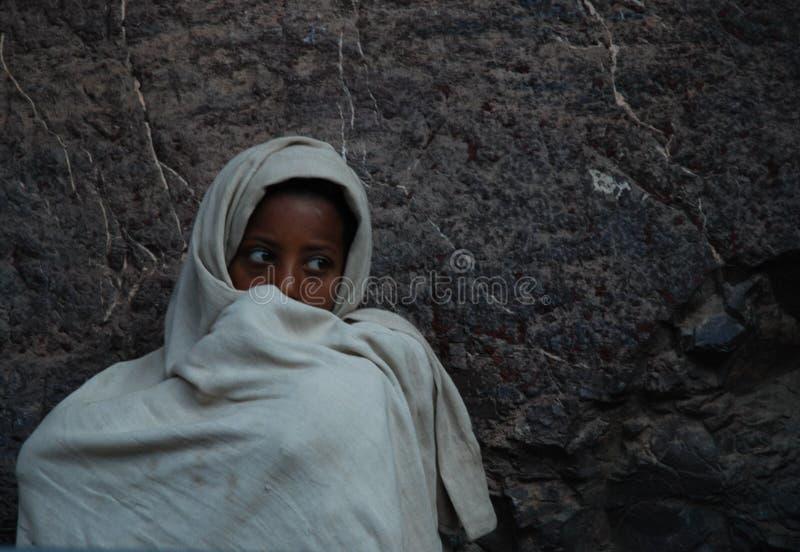 Lalibela, Wollo, Etiopia, circa febbraio 2007: Ragazzo che fissa mentre assistendo al servizio religioso immagini stock