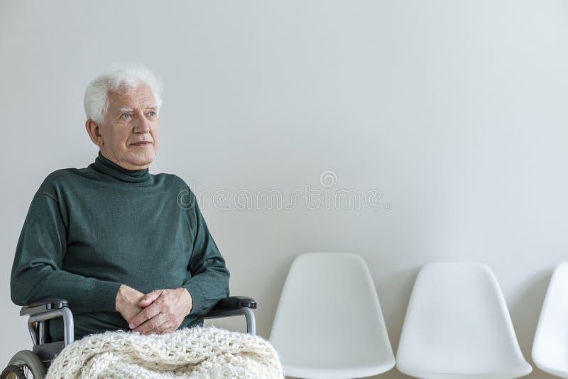 Lam man i en rullstol i ett väntande rum i ett sjukhus royaltyfri bild