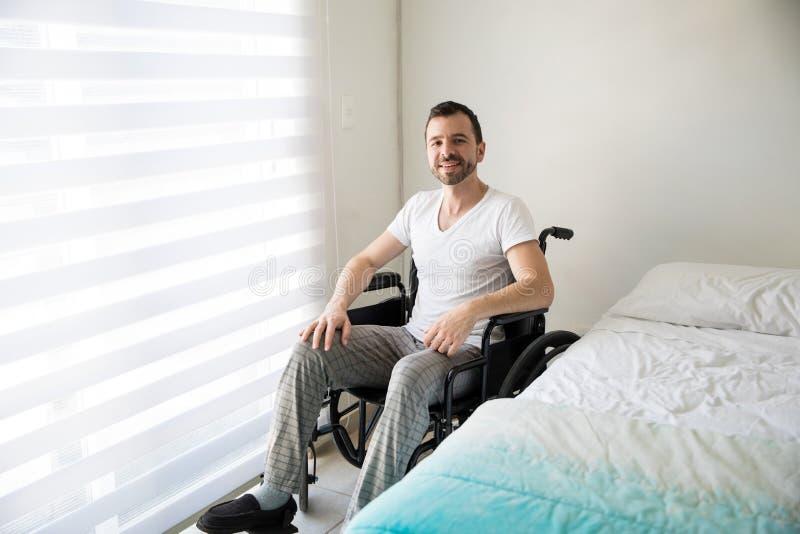 Lam man på en rullstol hemma royaltyfri bild