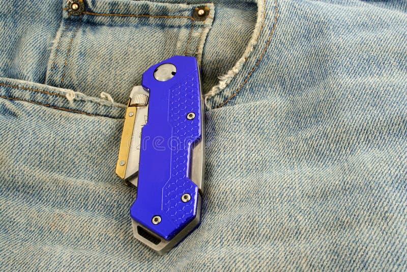 Lama anodizzata blu del rasoio degli appaltatori sui jeans immagini stock