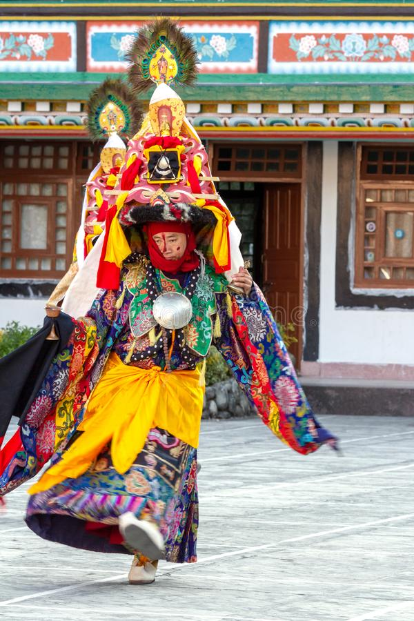 Lama in ritual costume and ornate hat performs Black Hat Dance of Tibetan Buddhism on the Cham Dance Festival royalty free stock photo