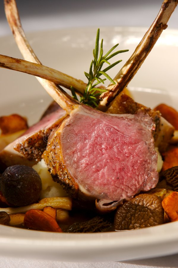 Lamb. Roasted rack of Lamb on a bed of mushrooms royalty free stock photography