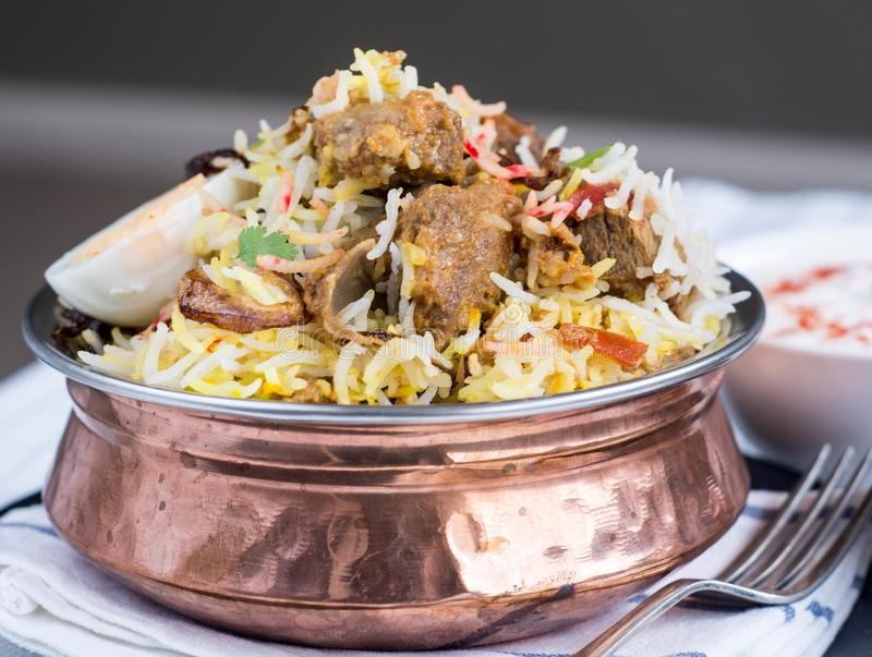 Lamb Biryani. Lamb or Mutton Biryani a festive Indian curry with crisp onion rings, coriander and egg, with raita royalty free stock image