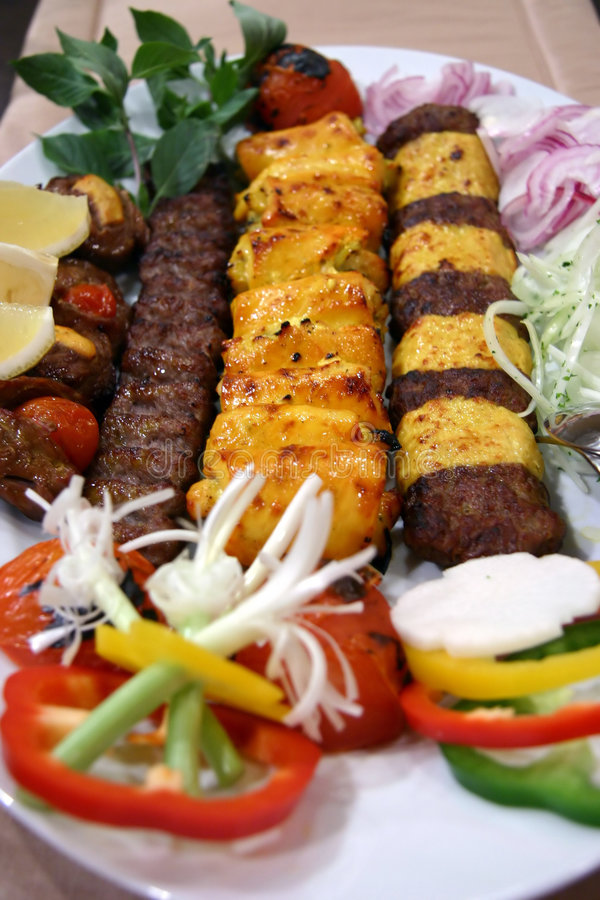 Lamb and chicken kebabs. Long strips of lamb and chicken kebabs with relish, slice onions, turnip, capsicum, mint leaves and lemon wedges stock photography