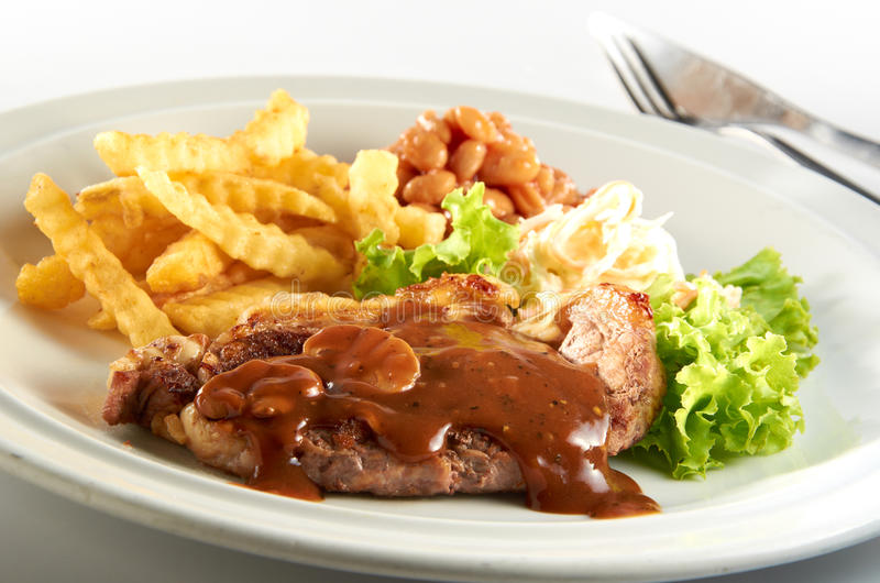 Lamb Chop. With mushroom sauce, baked bean, salad and potato chip serve on white plate royalty free stock image