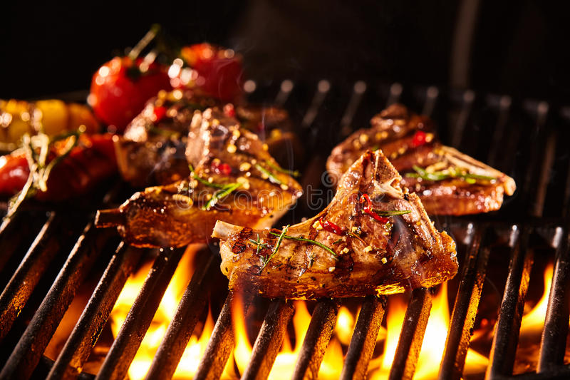 Lamb chop being grilled under flames royalty free stock images