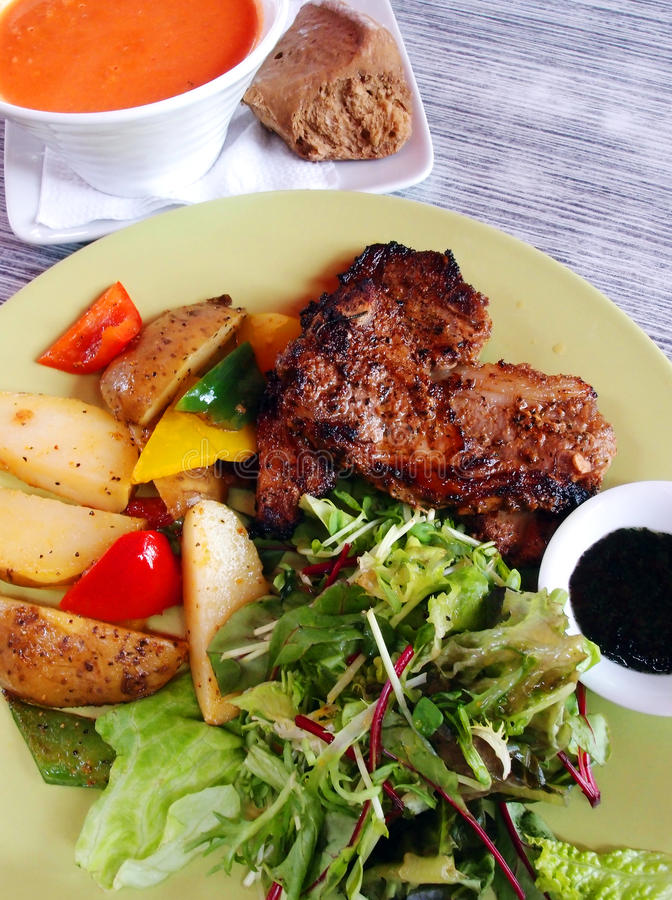 Lamb chop meal with soup and salad stock image