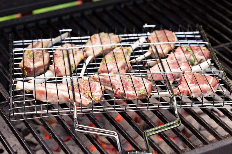 Lamb chops in grilling basket on grill stock images