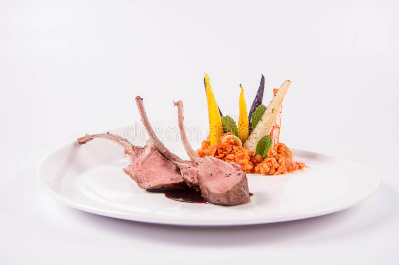 Lamb chops and lentils. Lamb chops, braised lentils with mint, roast vegetables and rosemary sauce on a white background royalty free stock photos