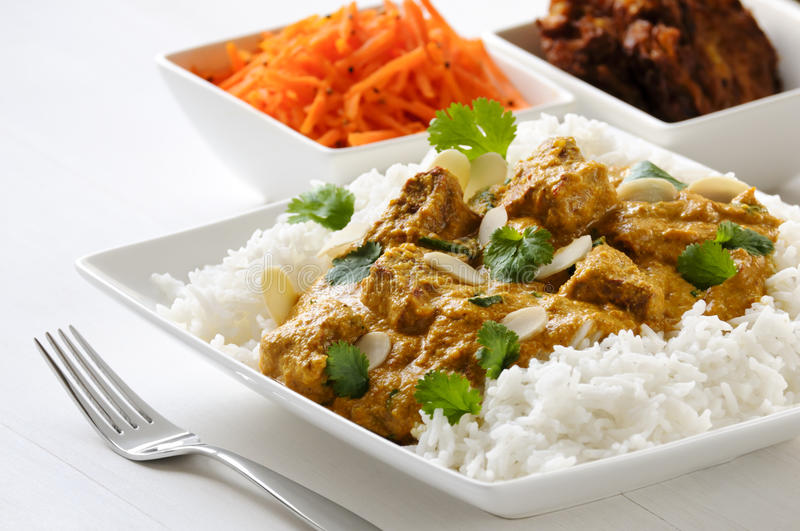 Lamb curry with rice. Curry meal - lamb pasanda with rice, bhaji and carrot salad behind stock photography