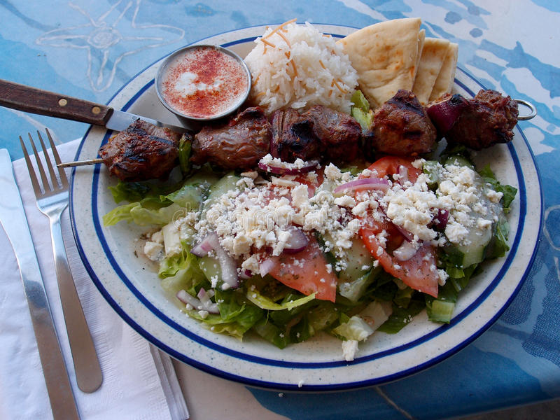 Lamb Kabob Plate. Grilled chunks of marinated lamb served with basamati rice, greek salad, pita, and yogurt sauce. With napkin, fork, knife, and steak knife royalty free stock photography