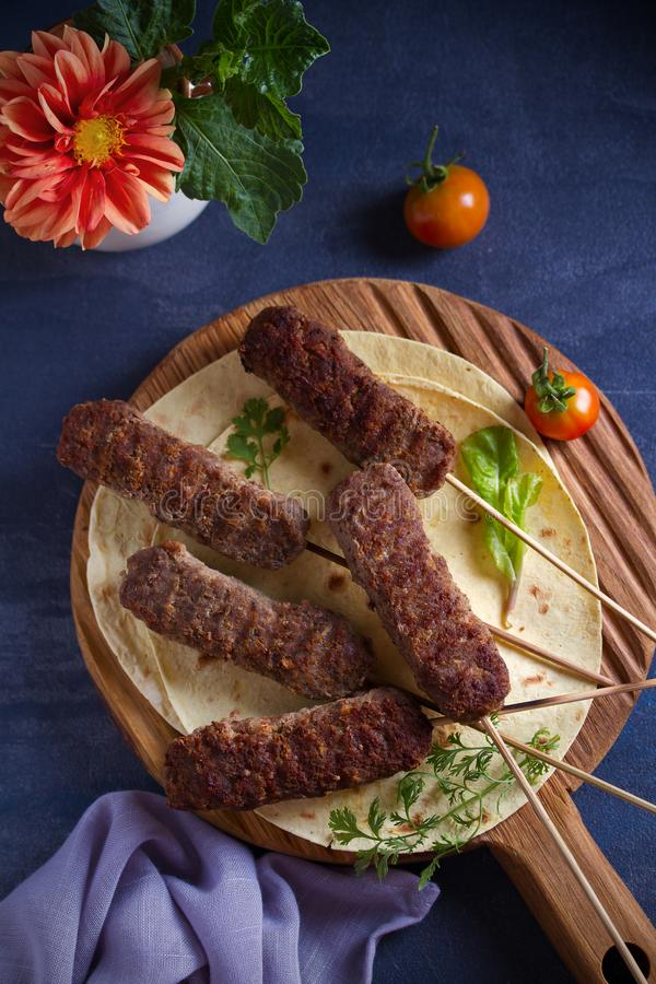 Lamb kebabs on serving board with pita bread, vegetables and yogurt sauce. stock photo