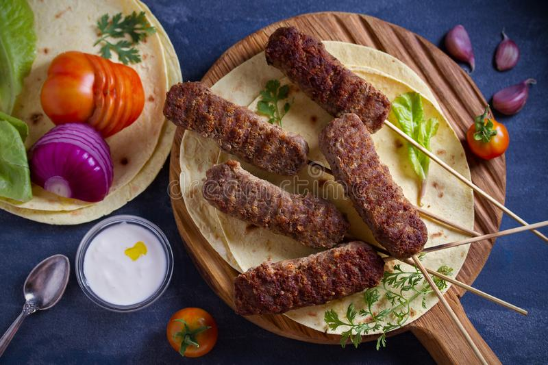 Lamb kebabs on serving board with pita bread, vegetables and yogurt sauce. stock photography